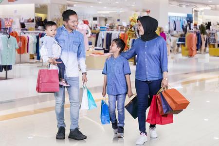 Obraz szczęśliwej rodziny muzułmańskiej trzymającej torby na zakupy podczas wspólnego spaceru po centrum handlowym Zdjęcie Seryjne