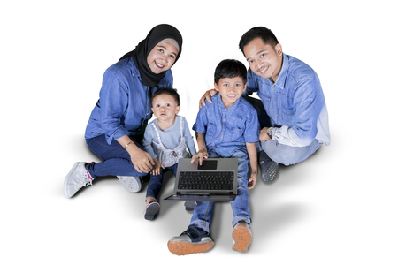 Top view of two children using a laptop with their parents while sitting in the studio, isolated on white background