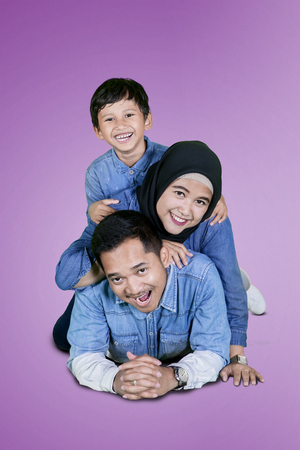 Portrait of young man having fun with his son and wife while lying in the studio with purple background