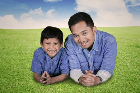 Image of a happy father looking at the camera while lying with his son in the meadow Stock Photo