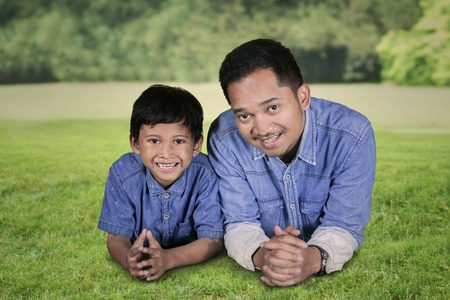 Close up of young man smiling at the camera while lying with his son on the green grass. Shot in the park