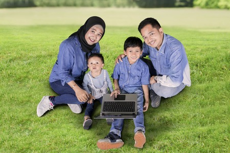 Top view of young parents and their children using a laptop while sitting together in the park Stock Photo