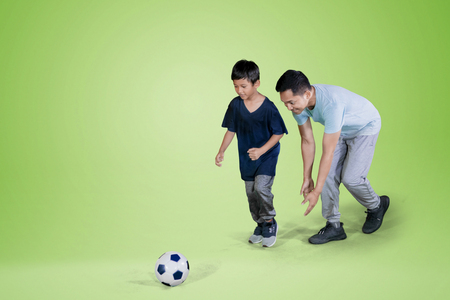 Picture of young man and his son playing football in the studio with green screen Фото со стока