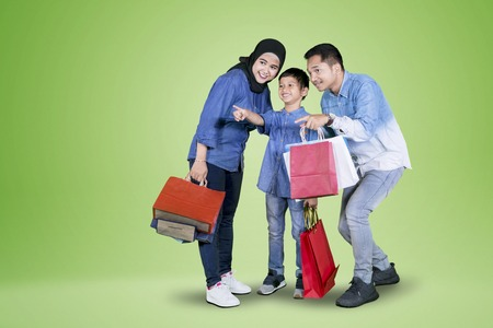 Picture of happy little boy pointing something while shopping with his parents in the studio Stockfoto - 115183403