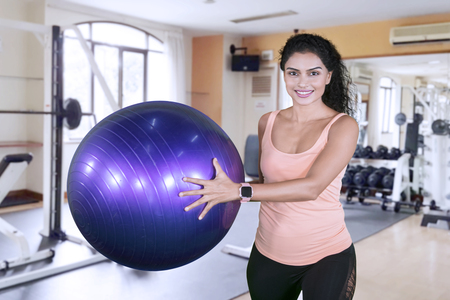 Picture of sporty woman smiling at the camera while holding a yoga ball in the fitness center