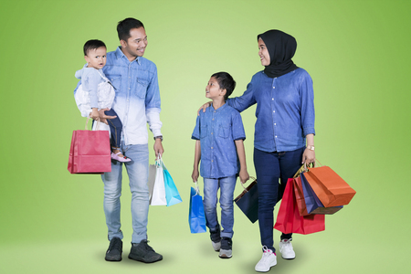 Picture of young Muslim family holding shopping bags while walking together in the studio with green screen