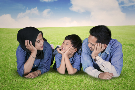 Image of young parents speaking with their son while lying together in the meadow Stock Photo