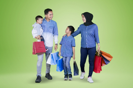Picture of young happy family carrying shopping bags while walking together in the studio with green screen Фото со стока