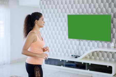 Pretty girl wearing sportswear while exercising in the front of the television. Shot at home Stock Photo
