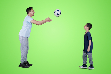 Picture of young man throwing a soccer ball to his son while playing in the studio with green screen Banco de Imagens - 115910439