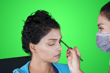 Image of India woman applied eyeshadow while doing makeup with her makeup artist in the studio