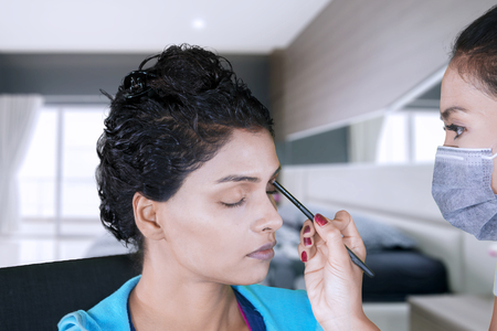 Close up of a young woman applied eyeshadow while doing makeup with her friend in the bedroom