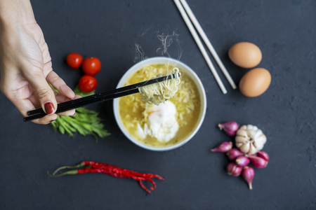 Close up of unknown woman hands holding boiled noodle with chopstick