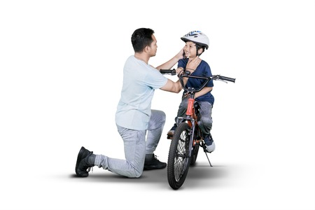 Young man helping his son to wear helmet before riding a bicycle in the studio, isolated on white background