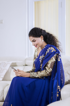 Picture of a pretty girl wearing blue saree clothes while using a mobile phone at home