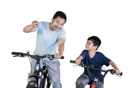 Picture of young man pointing at something while riding a bicycle with his son in the studio