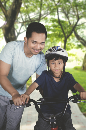 Portrait of little boy learn to ride bicycle with his father at the park. Shot outdoors Reklamní fotografie - 115910491