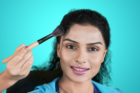 Closeup of pretty girl applied powder by her makeup artist while doing makeup in the studio