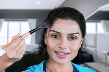 Closeup of happy woman applied powder by her makeup artist while doing makeup in the bedroom Stock fotó