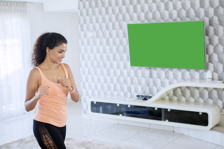 Image of Indian woman wearing sportswear while exercising in the front of the television. Shot at home