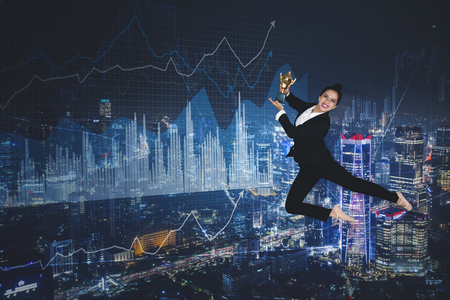Portrait of young businesswoman looks happy while holding a trophy and dancing in the sky at night time Imagens