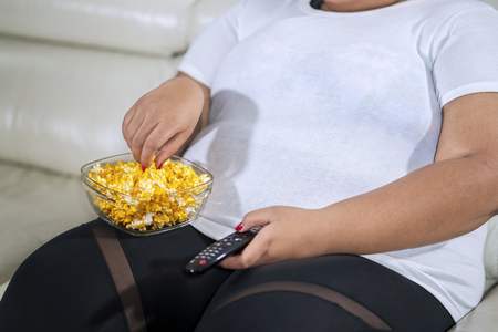 Close up of unknown fat woman enjoying a bowl of popcorn while watching television in the living room