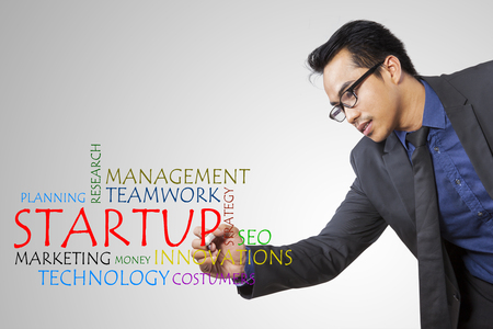 Image of Asian male entrepreneur writing word of startup on the transparent screen