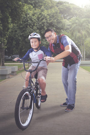 Picture of happy father guiding his son to riding a bicycle in the park. Shot at summer time Reklamní fotografie - 116624806