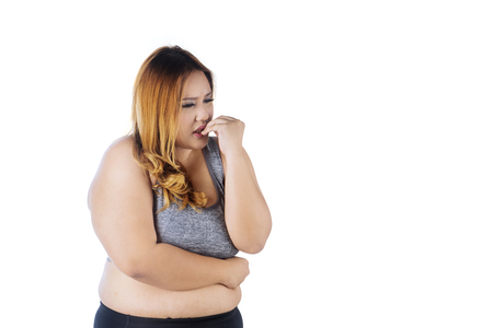 Caucasian obese woman looks anxious while standing in the studio and biting her fingernails , isolated on white background Stock Photo