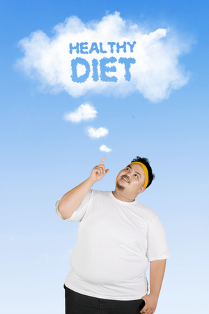Image of a young fat man pointing a cloud with healthy diet text on a cloud while standing under blue sky