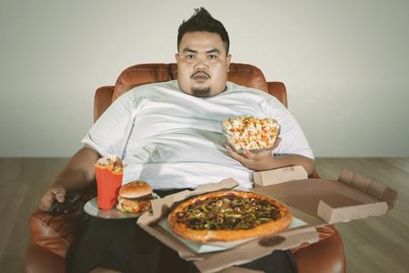 Imagen de un hombre obeso viendo la televisión en el sofá mientras come comida chatarra en casa