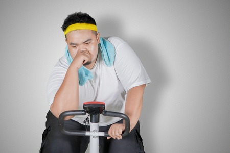 Image of tired obese man doing workout with exercise bike in the studio