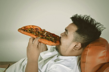 Close up of a young fat man relaxing on the sofa while eating a big pizza