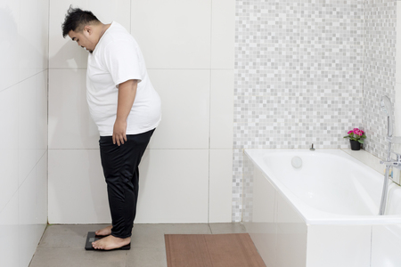 Picture of young fat man checking his weight while standing on the scale. Shot in the bathroom