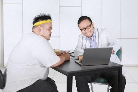 Male doctor discussing an examination result with his fat patient in the clinic