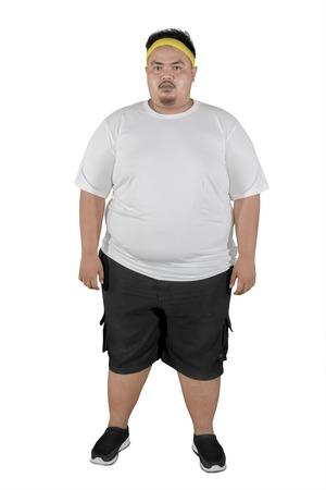 Volle Länge eines jungen dicken Mannes, der Sportkleidung trägt, während er im Studio steht, isoliert auf weißem Hintergrund