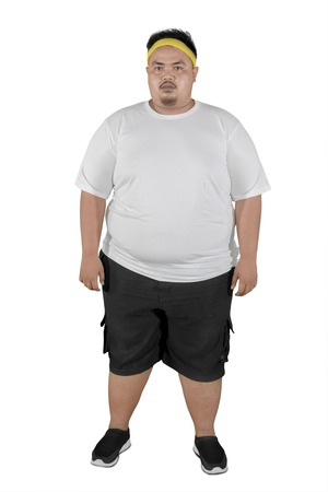 Volledige lengte van een jonge dikke man die sportkleding draagt terwijl hij in de studio staat, geïsoleerd op een witte achtergrond