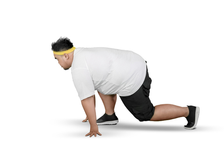 Side view of a young obese man ready to run while kneeling in the studio, isolated on white background 版權商用圖片