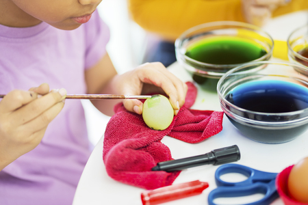 Hands of little girl dyeing eggs during preparing for Easter at home 版權商用圖片