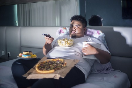 Unhealthy lifestyle concept: Asian fat man eating junk foods while watching TV in bed before sleep Imagens