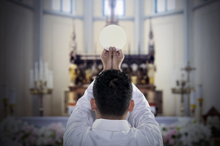 Back view of pastor raising a sacramental bread during celebrating a mass in the church
