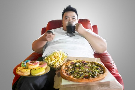Young obese man drinking a glass of coke and overeating during watching television in the studio 免版税图像