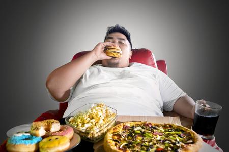 Das Bild des asiatischen dicken Mannes sieht gierig aus, während er Junk-Food auf dem Sofa isst. Im dunklen Raum erschossen
