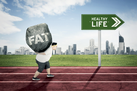 Picture of young obese man carrying a big rock with fat word while running on the track with text of healthy life on the signpost 版權商用圖片