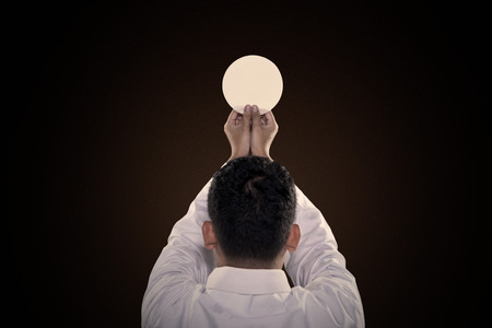 Rear view of pastor praying to God consecration a communion bread in the dark background
