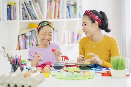 Photo d'une petite fille en train de teindre des œufs pour Pâques avec sa mère dans la bibliothèque