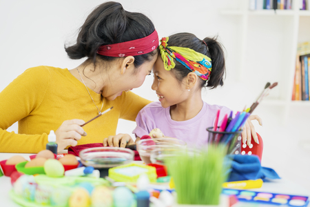 Picture of happy woman and her daughter painting eggs while doing preparation for Easter at home