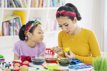 Beautiful mother teaching her daughter to dyeing Easter eggs while sitting at home