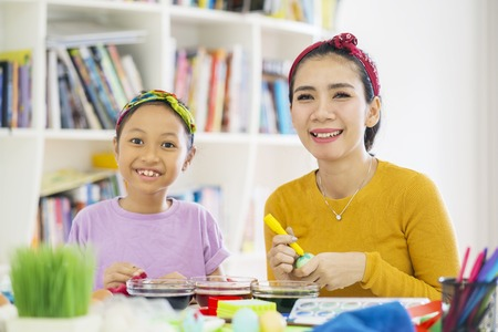 Picture of happy mother coloring eggs while preparing for Easter with her daughter at home