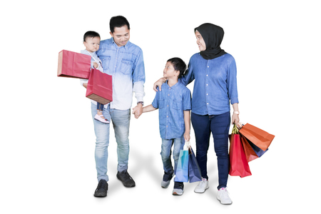 Full length of attractive family with two children holding shopping bags while walking isolated over white background